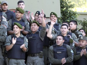 Argentine officers from the National Gendarmerie sing the national anthem during a nationwide protest outside their headquarters in Buenos Aires