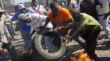 Protesters set tires alight during a street protest against President Michel Martelly's government to demand the cancellation of the Jan. 24, elections, in Port-au-Prince, Haiti, Monday, Jan. 18, 2016. Disputed election results have brought paralyzing street protests and many broad accusations of electoral fraud from civil society and opposition groups. (AP Photo/Dieu Nalio Chery)