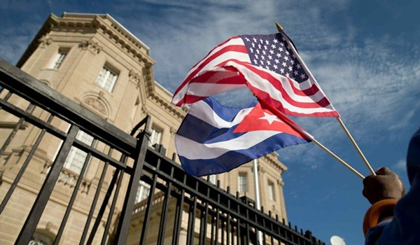 Edwardo Clark, a Cuban-American, holds an American flag and a Cuban flag as he celebrates outside the new Cuban embassy in Washington, Monday, July 20, 2015. The United States and Cuba restored full diplomatic relations Monday after more than five decades of frosty relations rooted in the Cold War. (AP Photo/Andrew Harnik)