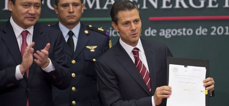 Mexican President Enrique Pena Nieto (C), next to Energy Secretary Pedro Joaquin Coldwell (R) and Mexican Interior Minister Miguel Osorio Chong (R), shows the bill of constitutional reform that would allow oil company Pemex to partner with private for exploration and extraction of hydrocarbons, keeping the company in the hands of the State in Mexico City, on August 12, 2013. AFP PHOTO/RONALDO SCHEMIDT        (Photo credit should read Ronaldo Schemidt/AFP/Getty Images)
