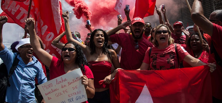 """Supporters of the ruling Worker's Party and former Brazilian President Luiz Inacio Lula da Silva demonstrate in his support and against O'Globo, in front of the Brazilian newspaper's headquarters in Rio de Janeiro on March 6, 2016. Brazil's ex-president Lula da Silva vowed to battle his opponents in the streets in a defiant speech late Friday, hours after being briefly detained as part of a probe into a massive corruption scheme. Prosecutors said Lula was targeted as part of the Operation Car Wash investigation into a sprawling embezzlement and bribery conspiracy centred on the state oil giant Petrobras. Lula was not arrested, but held for questioning over alleged """"favors"""" received from corrupt construction companies implicated in a kickback scheme, prosecutors said.   AFP PHOTO / CHRISTOPHE SIMON"""