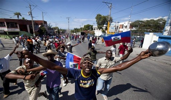 A protester holding a bowl and a spoon chants slogans against Haiti's President Michel Martelly on the anniversary of the Vertières battle in Port-au-Prince, Haiti, Monday, Nov. 18, 2013. The national holiday commemorates the battle that led to Haiti's independence from France in 1804. (AP Photo/Dieu Nalio Chery)