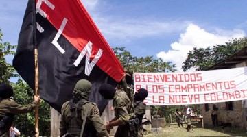 "Members of the National Liberation Army (ELN) set the organization's flag in San Francisco, a mountainous region in northern Colombia, where representatives of the government met with rebel leaders , Monday, Oct. 12, 1998. After the meeting the participants announced the call for a forum to meet February discuss peace prospects. With an estimated 5,000 fighters, the ELN is the country's second-largest guerrilla movement. The sign in the back reads ""Welcome to the camps for the new Colombia."" (AP Photo/Fernando Llano)"