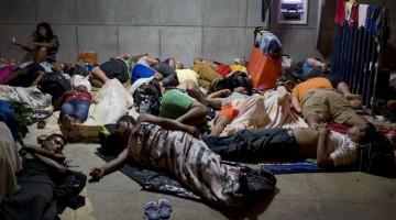 ARCHIVO - En esta fotografía de archivo tomada el 21 de noviembre de 2015, una inmigrante cubana usa su teléfono celular mientras otros cubanos duermen fuera del edificio del puerto fronterizo de Peñas Blancas, Costa Rica, en la frontera con Nicaragua, país que cerró sus fronteras a los inmigrantes isleños. El Ministerio de Relaciones Exteriores de Costa Rica dijo en un comunicado el 28 de diciembre que un primer traslado humanitario de cubanos hacía El Salvador se hará vía aérea en enero. Desde allí, podrán continuar en autobús hacia México. El número de cubanos varados en Costa Rica ha alcanzado al menos 8.000 desde que la vecina Nicaragua cerrara su frontera a los cubanos hace algunas semanas. (AP Foto/Esteban Felix, Archivo)