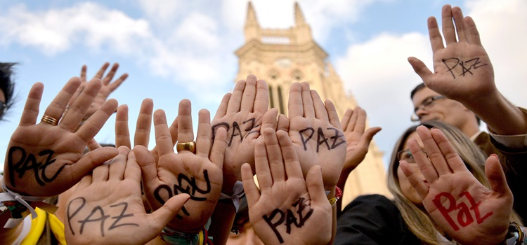 "zzzzinte1Supporters of Colombian president and presidential candidate Juan Manuel Santos raise their hands with the word ""Peace"" written on them during a peace event in Bogota, on June 11, 2014. Colombia's government and the country's second largest guerrilla group, the National Liberation Army (ELN), announced on the eve they have opened peace talks, which adds to those taking place with the FARC, with a tense runoff presidential election just days away. AFP PHOTO/Diana Sanchez zzzz"
