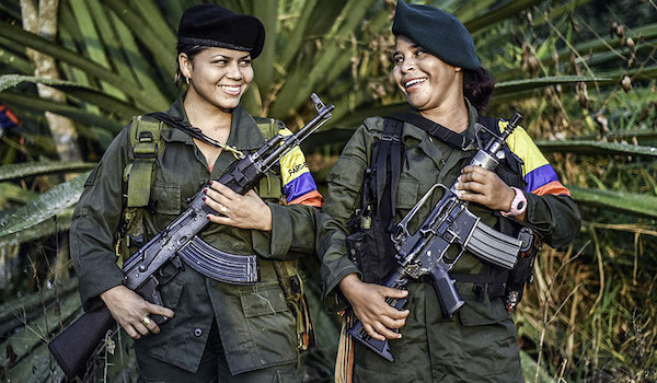 MAnuela (L) and Marta, members of the Revolutionary Armed Forces of Colombia (FARC), pose for a picture at a camp in the Colombian mountains on February 18, 2016. Many of these women are willing to be reunited with the children they gave birth and then left under protection of relatives or farmers, whenever the peace agreement will put an end to the country's internal conflict.    AFP PHOTO / LUIS ACOSTA
