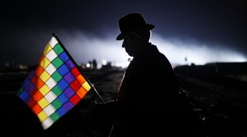 In this Jan. 21, 2016, photo, an Aymara man holding a Wiphala flag is silhouetted against an early morning sky as he waits for the arrival of Bolivia's President Evo Morales to take part in an Andean ritual honoring the 10 years Morales has served as leader of the South American country, at the archeological site Tiwanaku, Bolivia. Morales elevated the status of the multi-colored flag that represents the people of the Andes, making it the co-official flag of Bolivia. (AP Photo/Juan Karita)