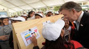El Presidente Juan Manuel Santos observa el dibujo de una niña que plasmó su idea sobre cómo será el país sin conflicto armado, en el lanzamiento del concurso 'Pinta una Colombia en Paz' efectuado hoy en la Casa de Nariño.