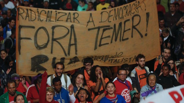 "Demonstrators march holding a banner that reads in Portuguese ""Temer Out,"" during a protest organized by the workers roofless movement, against Brazil's acting President Michel Temer, and in support of Brazil's suspended President Dilma Rousseff, in Sao Paulo, Brazil, Thursday, May 12, 2016. In his first words to Brazilians as acting president, the former vice president promised to beef up the fight against corruption, and in particular said he will support the sweeping investigation into a mammoth kickback scheme at state oil company Petrobras. Temer himself has been implicated by witnesses in the probe, though he has not been charged. (AP Photo/Andre Penner)"