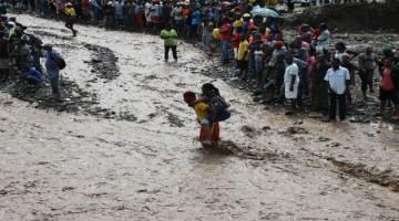 HAI01. PETIT GOAVE (HAITI), 05/10/16.- Personas intentan cruzar el río La Digue, debido al derrumbe del único puente que conecta con el sur, tras el paso del huracán Matthew hoy, 5 de octubre de 2016, en Petit Goave (Haití). El impacto del huracán Matthew en Haití, donde dejó al menos nueve muertos, miles de desplazados y comunidades incomunicadas, principalmente en el suroeste, obligó hoy a las autoridades electorales a aplazar los comicios del domingo. EFE/Orlando Barría