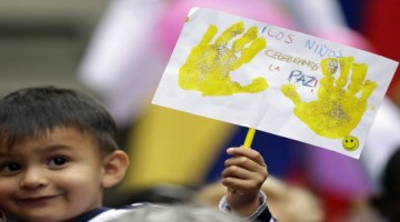 "A boy holds a sign that reads in Spanish ""Children celebrate peace"" during the celebration of the agreement between Revolutionary Armed Forces of Colombia, FARC, and Colombia's government, in Bogota, Colombia, Thursday, June 23, 2016. Colombian President Juan Manuel Santos and the head of the country's leftist FARC rebels agreed Thursday on a cease-fire and rebel disarmament deal that moves the country closer to ending a 52-year war that has left more than 220,000 people dead. (AP Photo/Fernando Vergara)"