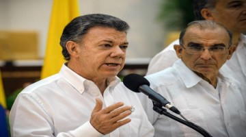 """Colombian President Juan Manuel Santos speaks next to the head of the Colombian government delegation for the peace talks with the Revolutionary Armed Forces of Colombia (FARC), Humberto de la Calle, during a press conference after a meeting with The head of the FARC guerrilla Timoleon Jimenez, aka Timochenko (out of frame) in Havana on September 23, 2015. The Colombian government and FARC rebels announced a key breakthrough in their nearly three-year peace talks Wednesday with the signing of a deal on justice for crimes committed during the five-decade conflict. The deal includes the creation of special courts and a broad amnesty, though this will not cover """"crimes against humanity, serious war crimes"""" and other offenses including kidnappings, extrajudicial executions and sexual abuse, said officials from Cuba and Norway, the guarantors in the talks. AFP PHOTO / Yamil Lage"""