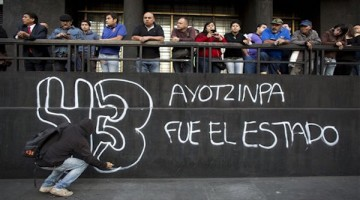 "A protestor paints graffiti reading ""43, Ayotzinapa was the State,"" accusing the government of being behind the disappearance of 43 teachers college students, during a demonstration in Mexico City, Monday, Dec. 1, 2014. Protesters marched in several cities in Mexico on Monday to mark the second anniversary of President Enrique Pena Nieto's administration and demand the government find 43 students who disappeared at the hands of police. (AP Photo/Rebecca Blackwell)"