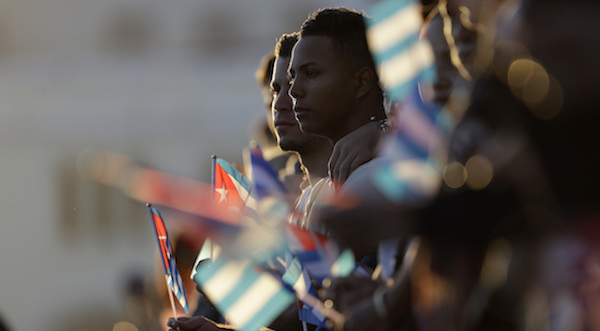 People line the Malecon seaside boulevard holding Cuban flags as they wait for the motorcade transporting the remains of Cuban leader Fidel Castro in Havana, Cuba, Wednesday, Nov. 30, 2016. Castro's ashes have begun a four-day journey across Cuba from Havana to their final resting place in the eastern city of Santiago. (AP Photo/Natacha Pisarenko)