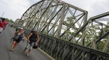 PA3002 - SIXAOLA (PANAMÁ), 14/12/2016.- Turistas cruzan el puente binacional centenario sobre el río Sixaola hoy, miércoles 14 de diciembre de 2016, en Sixaola, frontera entre Panamá y Costa Rica. Las autoridades de Panamá y Costa Rica entregaron hoy la orden de proceder para la construcción de un moderno puente binacional con coste de 17,5 millones de dólares y con el que aspiran impulsar el comercio y el turismo entre los dos países. EFE/Arturo Wong