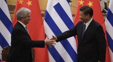 Uruguay's President Tabare Vazquez (L) shakes hands with Chinese President Xi Jinping during a signing ceremony at the Great Hall of the People in Beijing on October 18, 2016. / AFP PHOTO / POOL / Naohiko Hatta